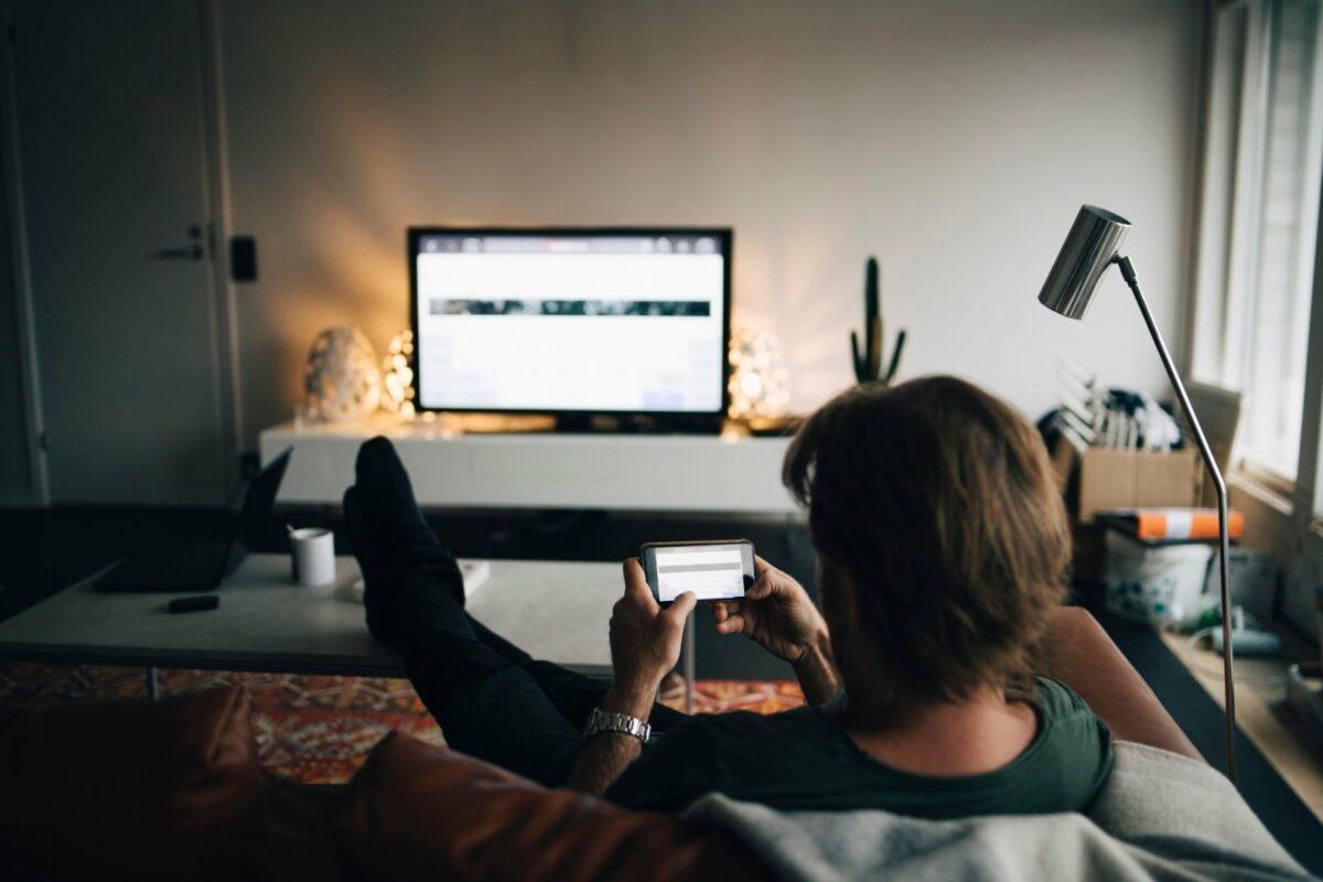 Mann sitzt mit Handy vor dem Fernseher