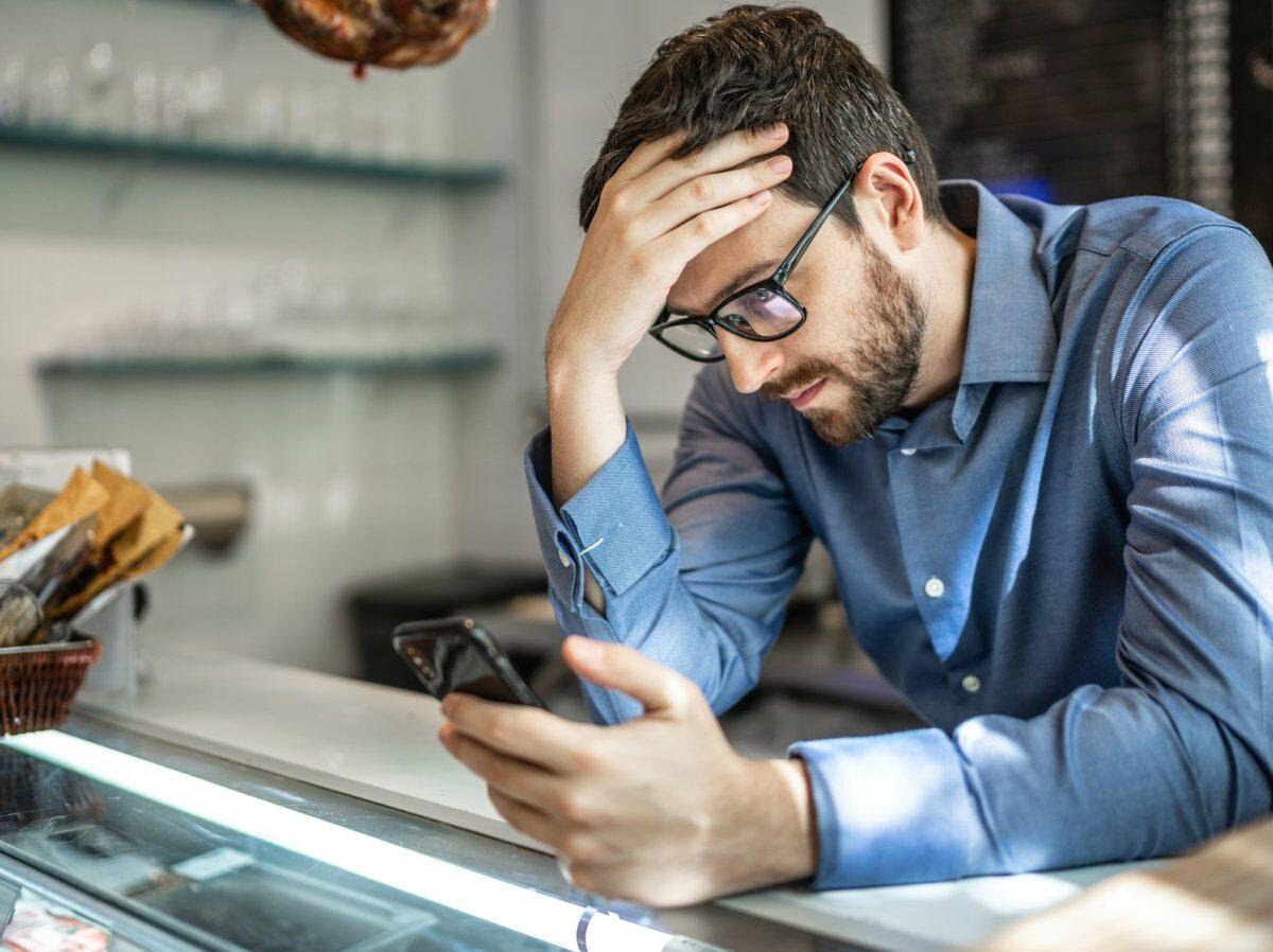 Mann nachdenklich mit Handy.