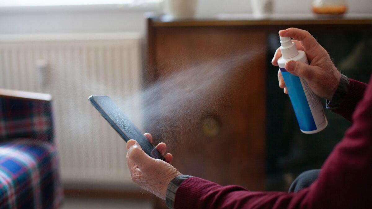 Jemand reinigt das Handy mit Spray.