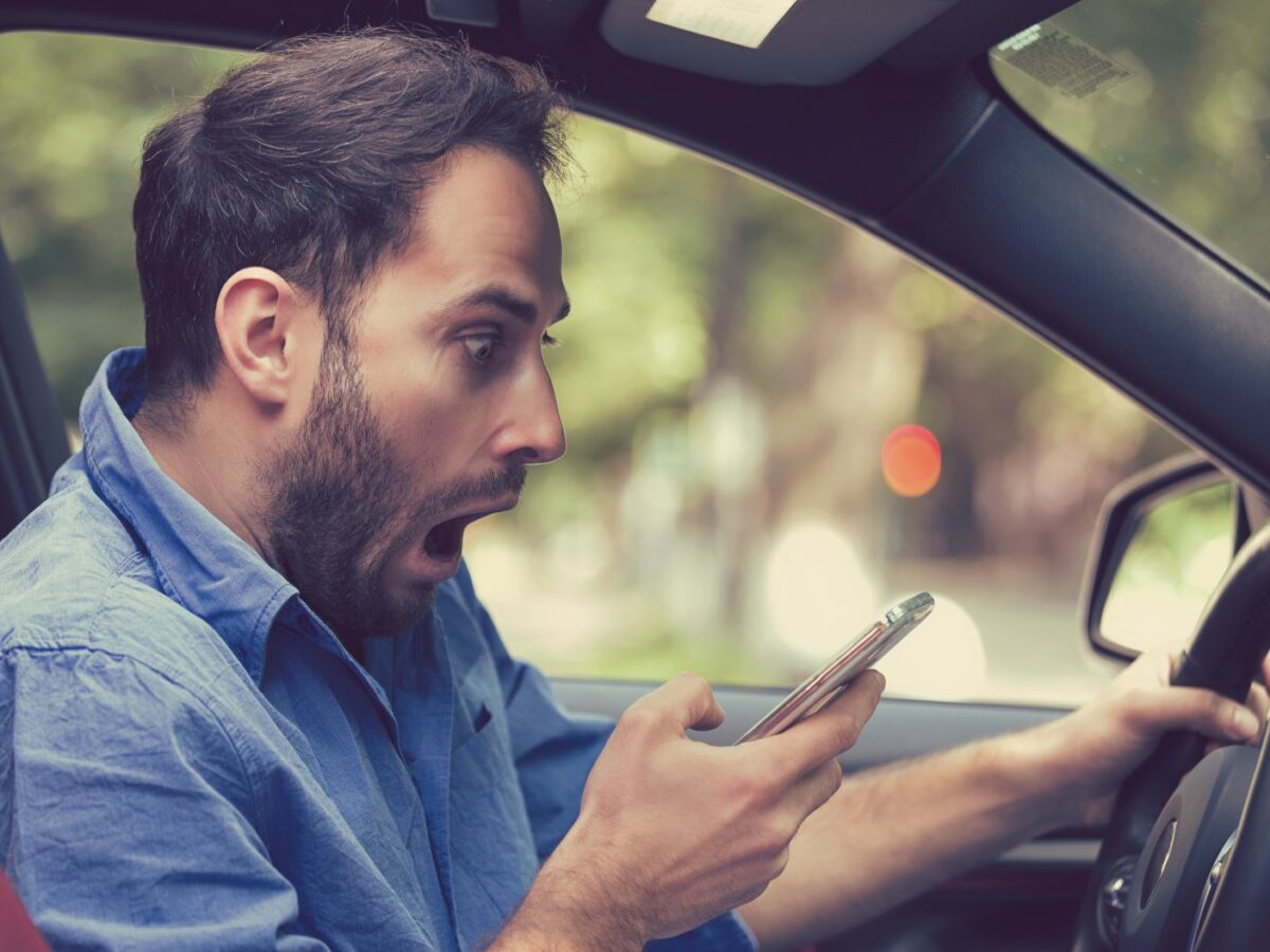 Mann schaut geschockt aufs Handy in seinem Auto.
