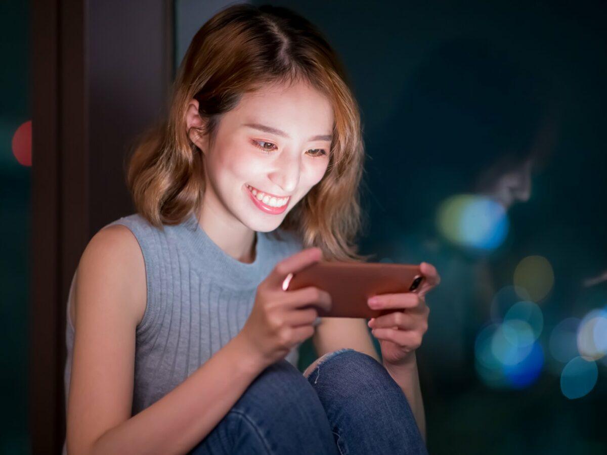 Frau spielt am Handy.