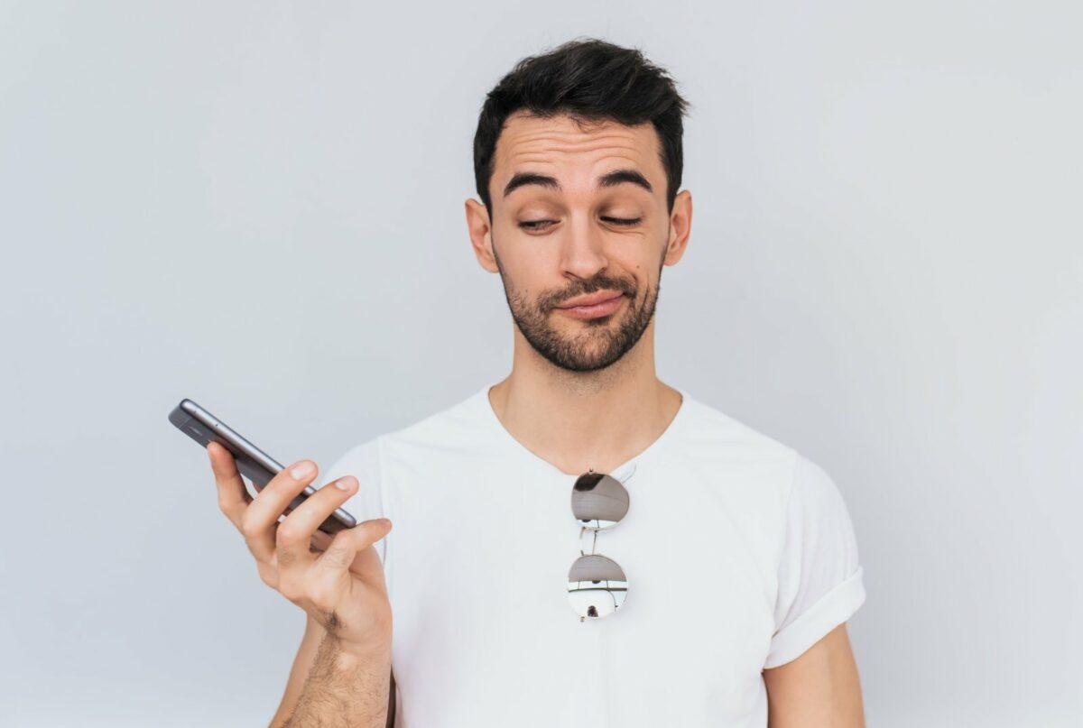 Mann guckt aufs Handy.