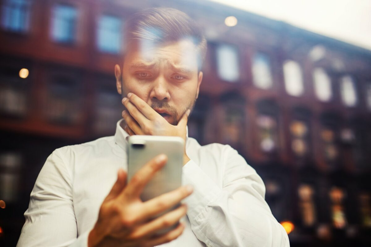Mann schaut erschrocken aufs Handy.