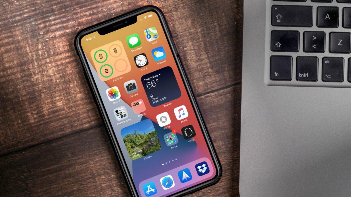iPhone mit iOS 14 neben einem MacBook.