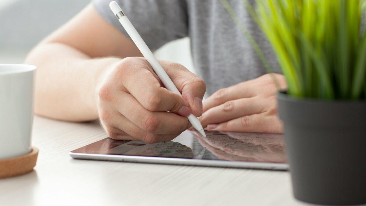 Person schreibt auf iPad