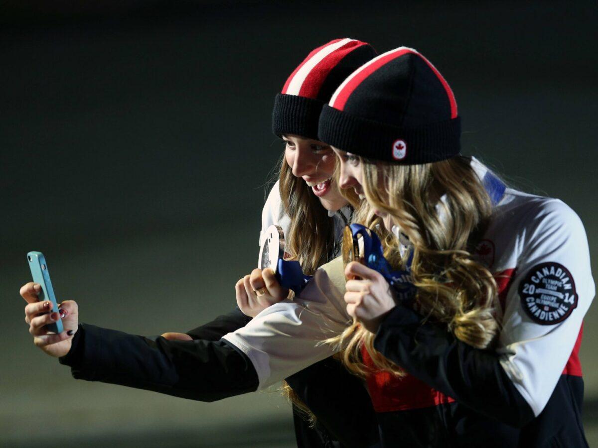 Zwei Frauen mit Olympia-Medaillen schießen mit dem iPhone ein gemeinsames Selfie