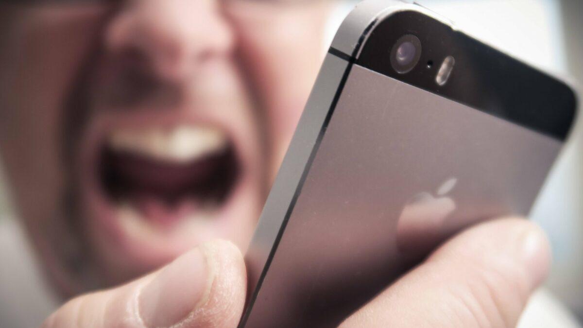 Ein Mann schreit sein iPhone an.