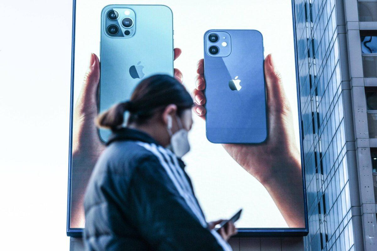Frau vor einem Wahlplakat für das  iPhone12