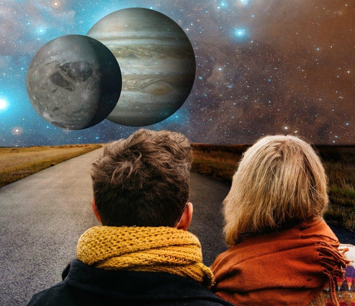 Mann und Frau stehen auf einer Straße und sehen ins All mit zwei Planeten