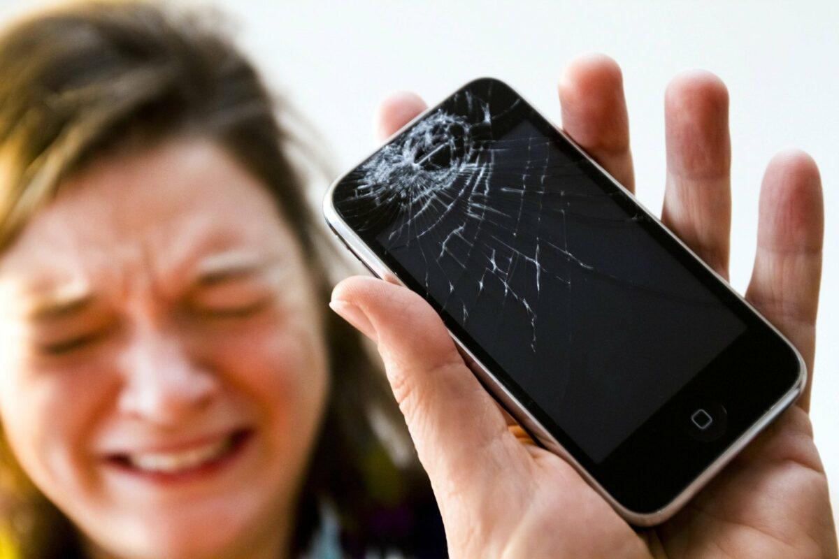 Eine Frau weint und hält ein kaputtes iPhone in der Hand.