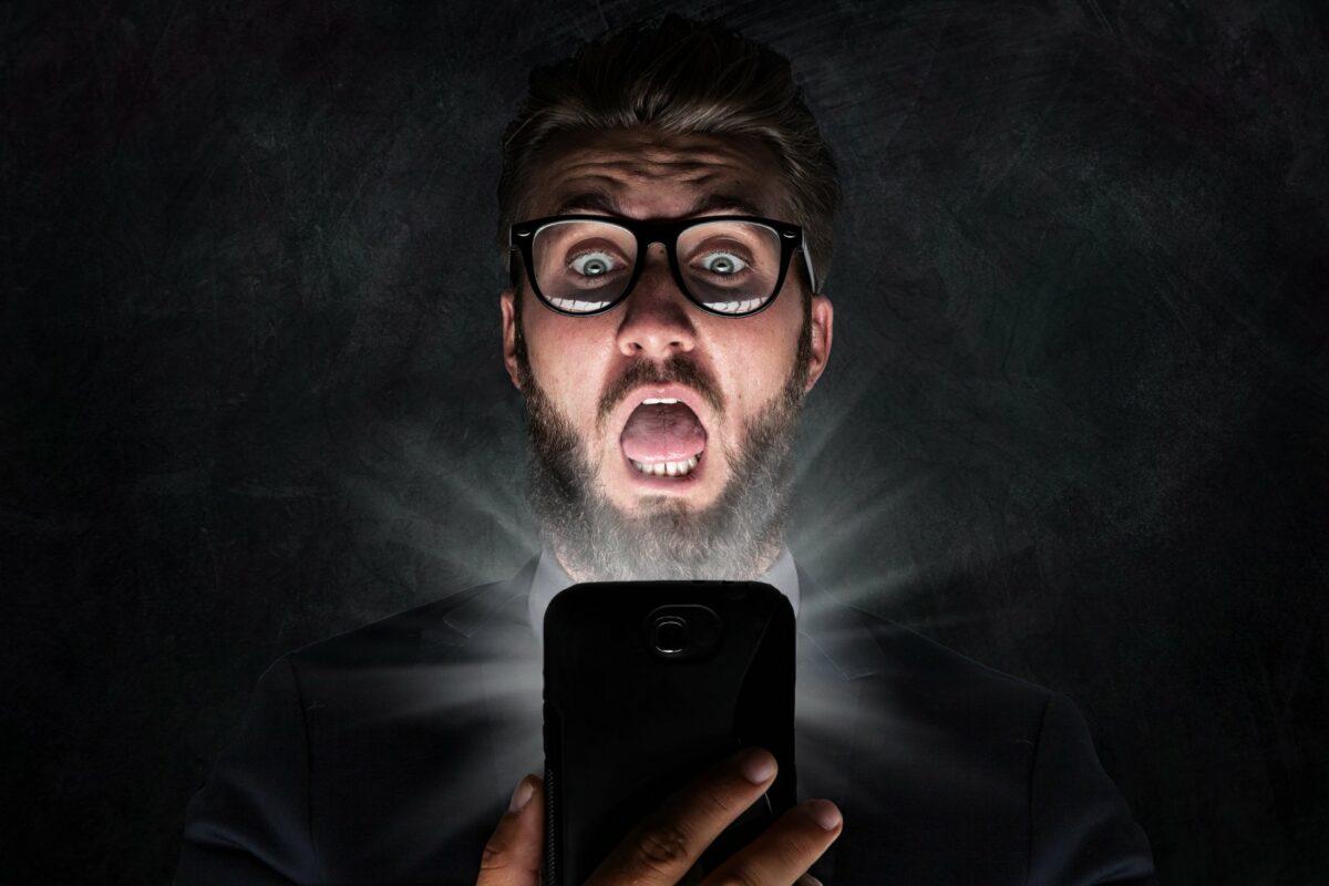 Mann ist von iPhone geschockt.