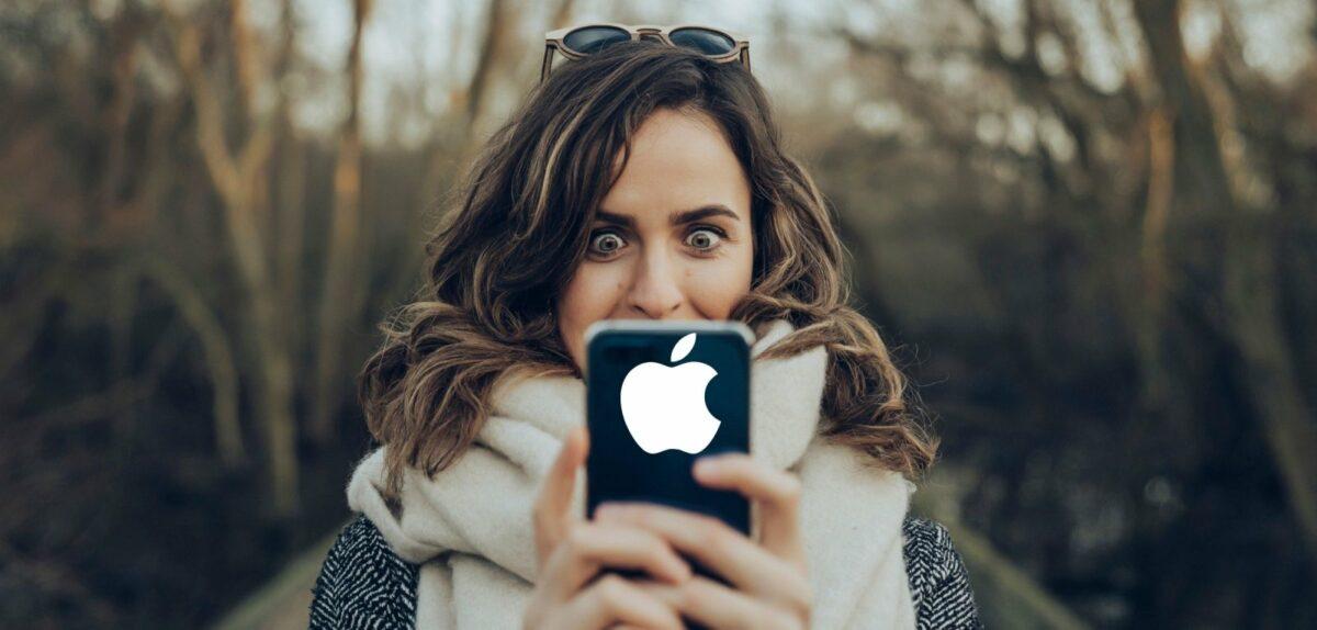 Frau blickt überrascht auf ihr Handy.