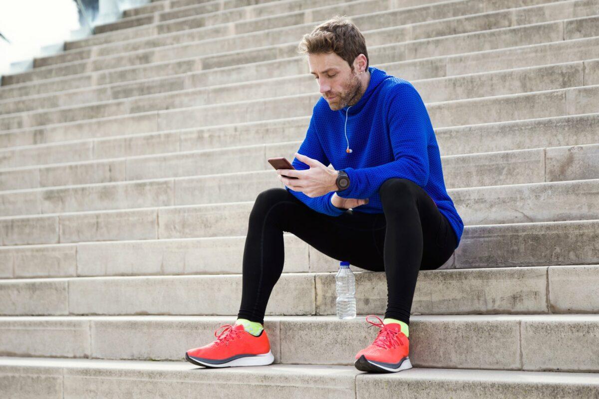 Mann sitzt auf Treppe und guckt auf iPhone.