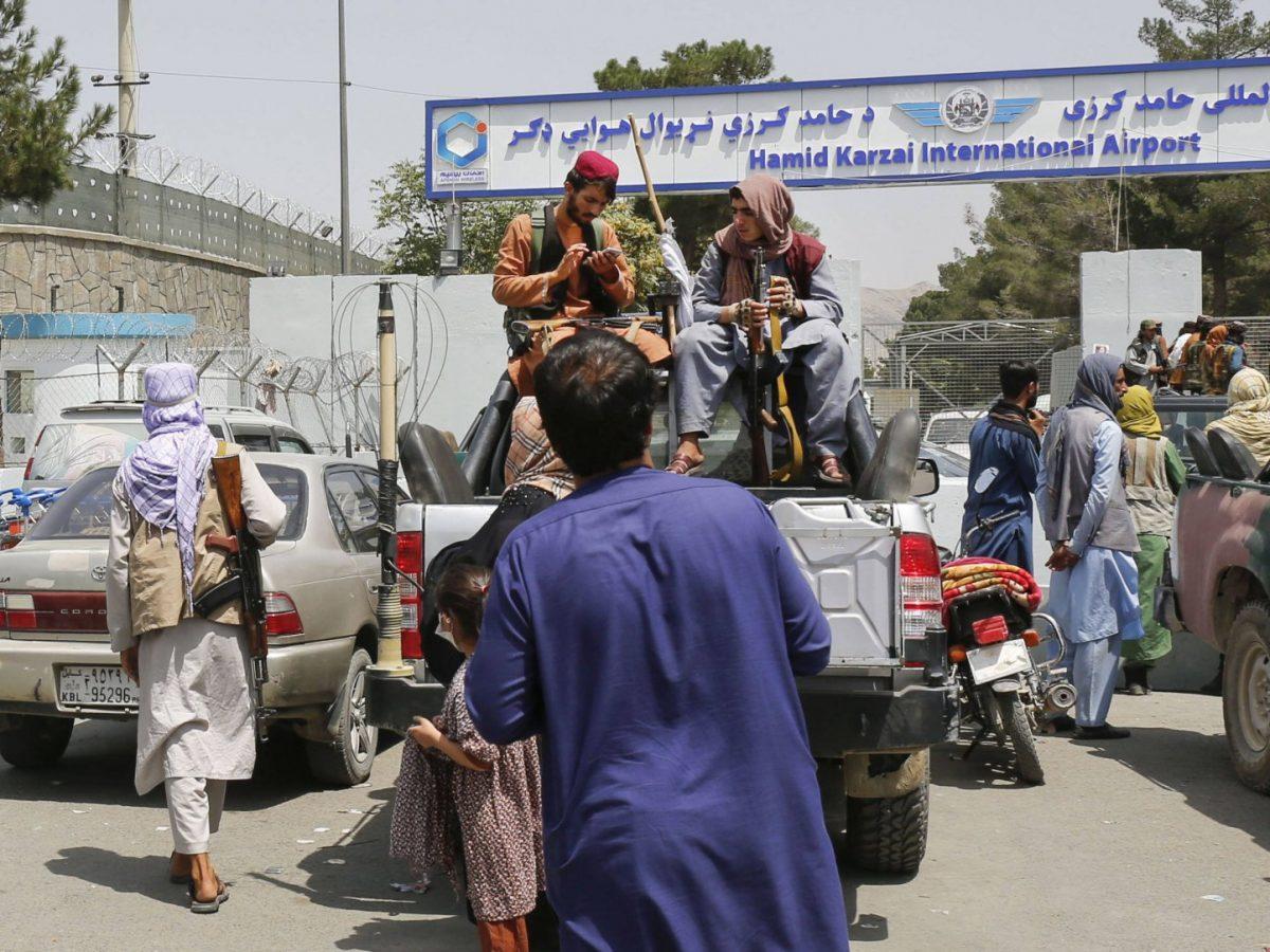 Männer mit Waffen sitzen auf einem Auto vor einem Flughafen in Kabul am 17. August 2021.