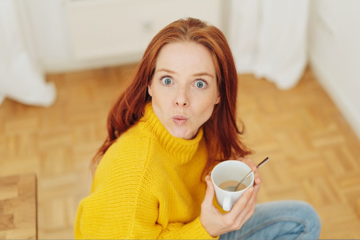 Frau mit Kaffee schaut überrascht