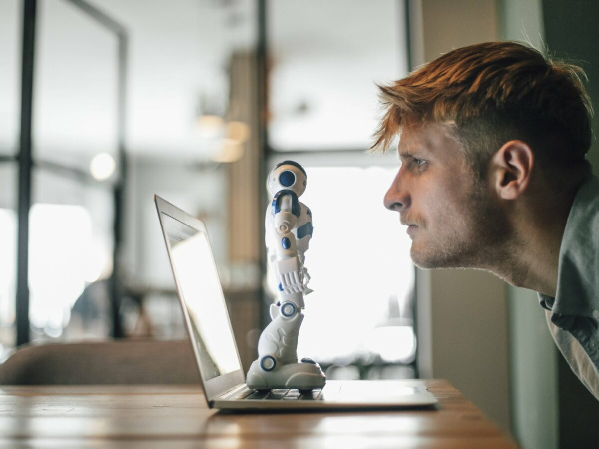 Mann starrt auf Roboter am Rechner
