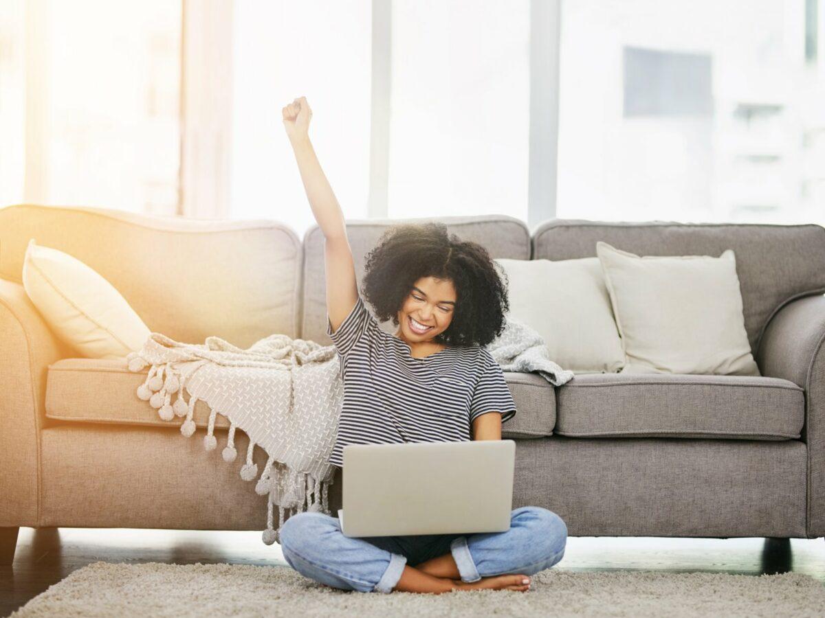 Frau sitzt mit Laptop auf dem Schoß vor dem Sofa auf dem Boden und freut sich.