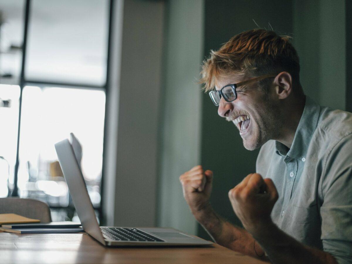 Ein Mann am Laptop freut sich.