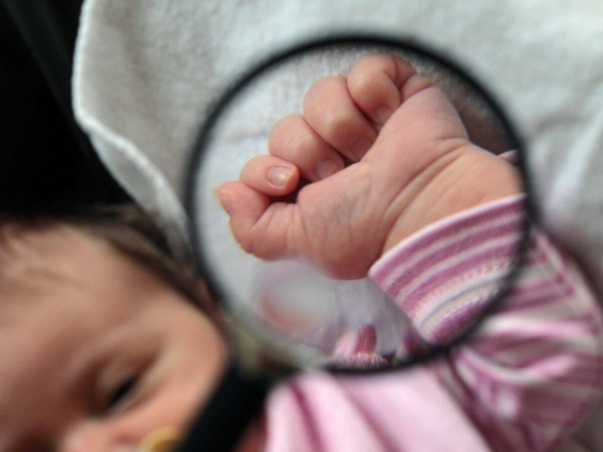 Lupe auf eine Babyhand