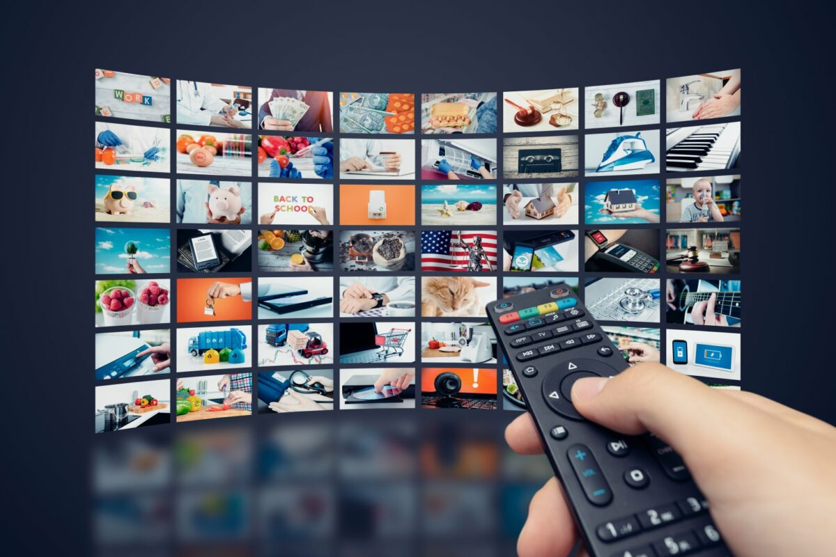 Eine Multimedia-Videowand mit einer Fernbedienung die darauf zeigt.