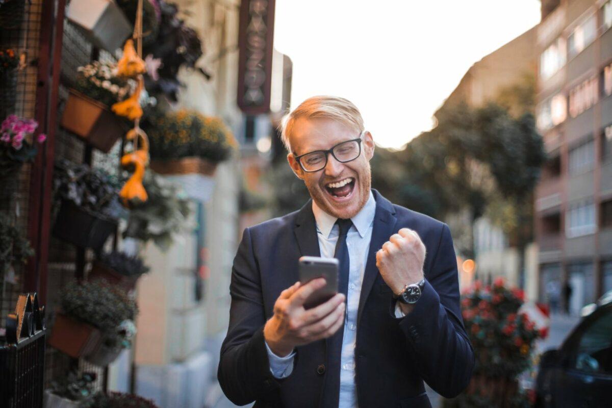 Ein glücklicher Mann mit Handy in der Hand