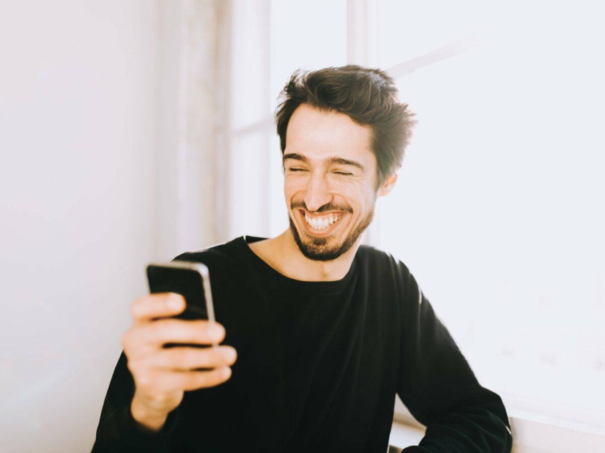 Mann am Handy grinst