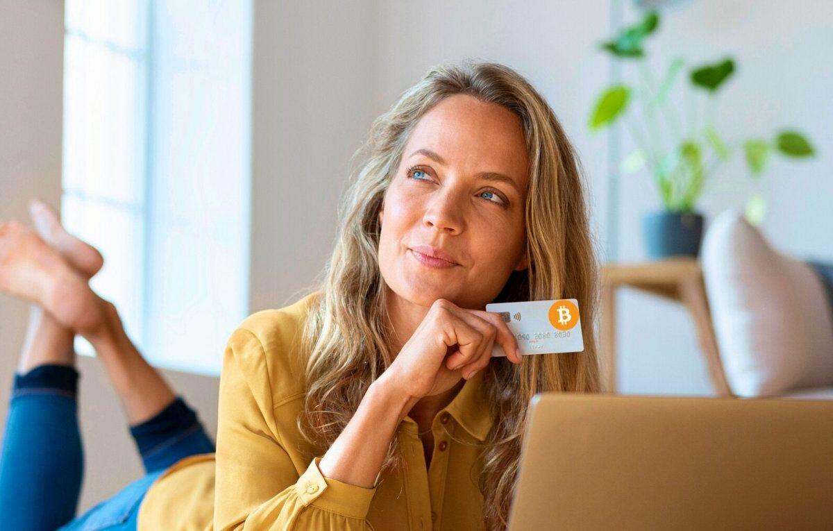 Frau mit Kreditkarte vor einem Laptop