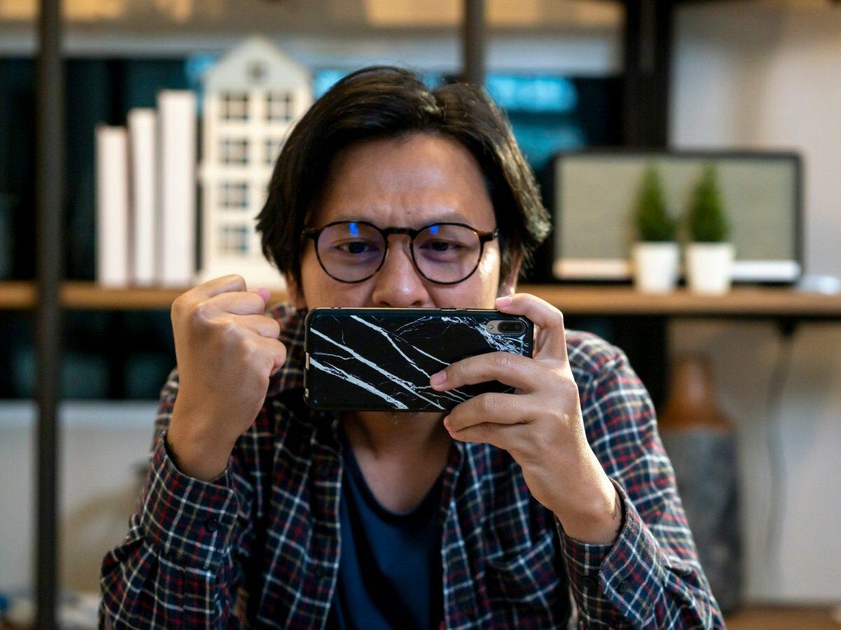 Mann spielt am Handy.