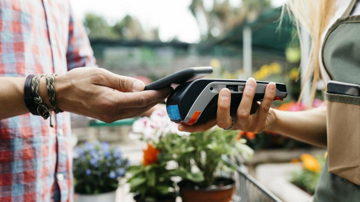 Ein Kunde zahlt auf dem Wochenmarkt mit seinem Smartphone