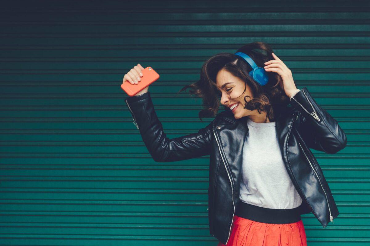 Frau tanzt mit Kopfhörern zur Musik ihres Handys.