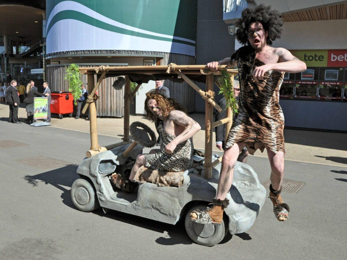 Männer als Neandertaler verkleidet fahren auf Steinzeit-Mobil.