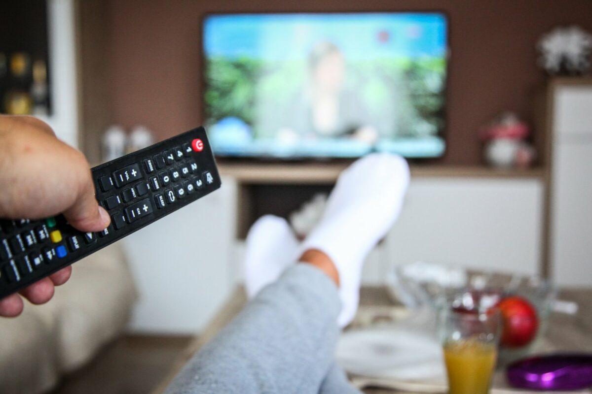 Mensch mit Fernbedienung vor dem Fernseher