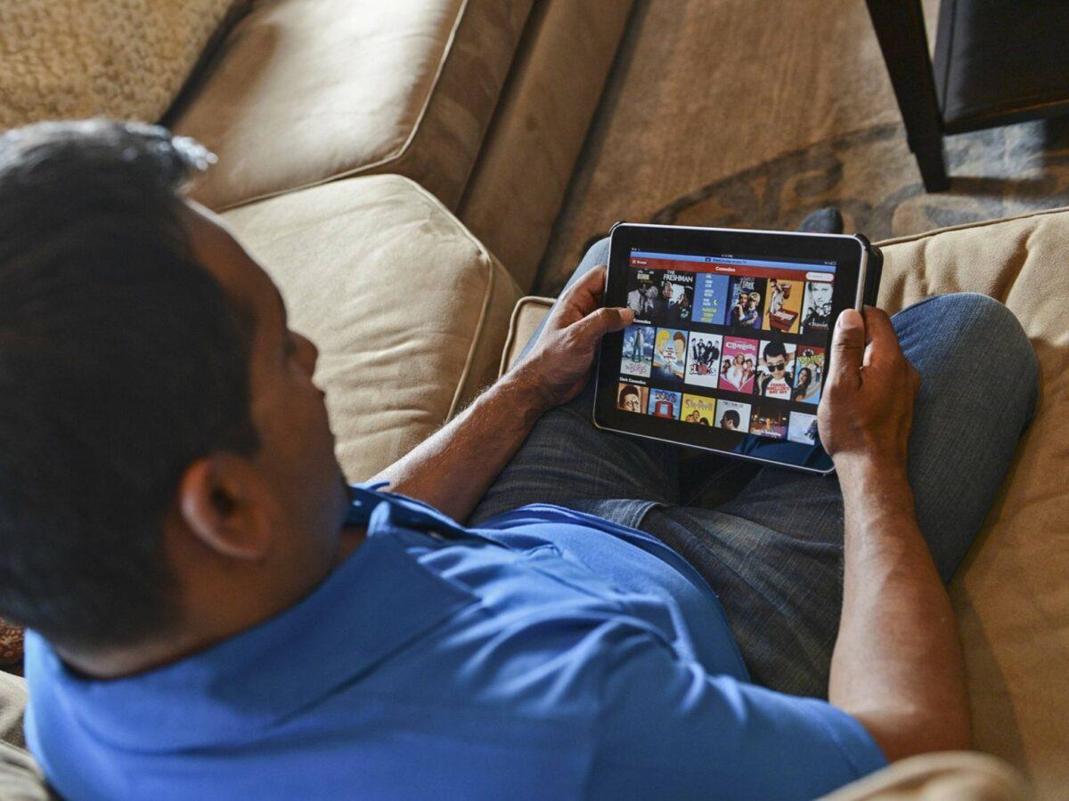 Ein Mann schaut auf seinem Tablet Netflix.