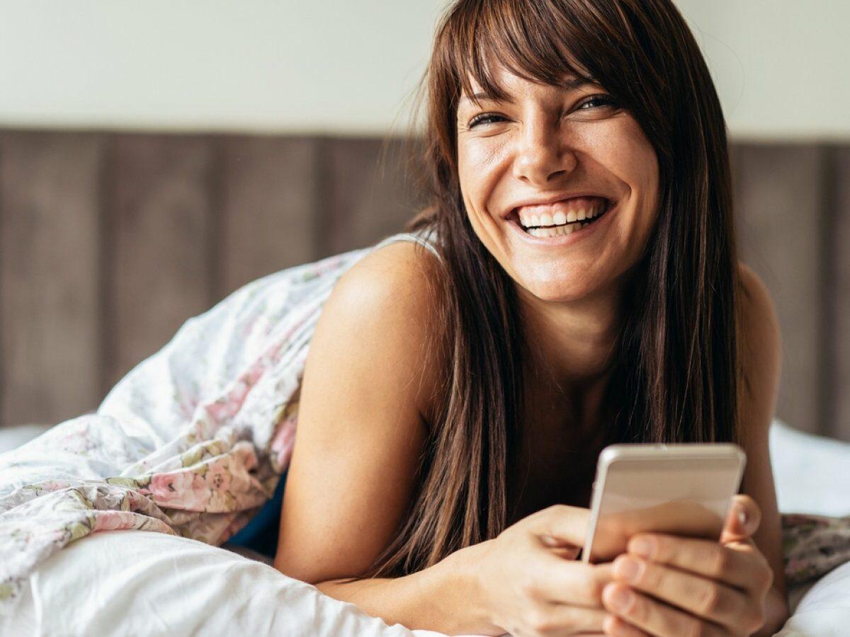 Frau mit Handy in der Hand im Bett.