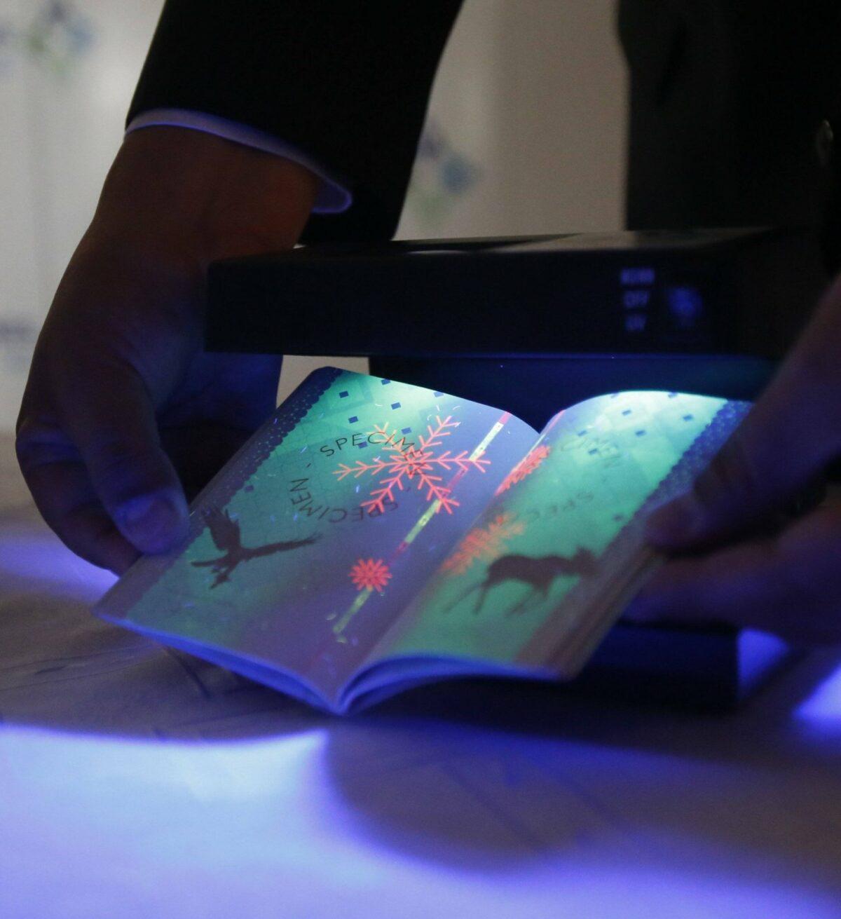 Person hält Pass unter Schwarzlicht