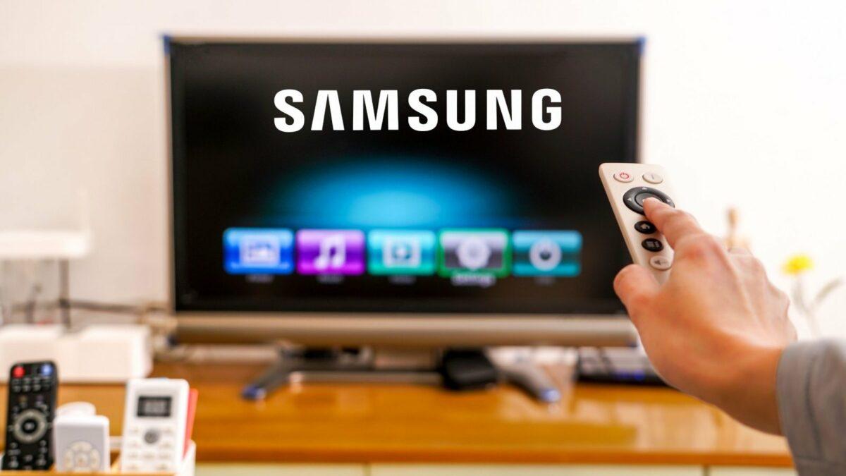 Eine Fernbedienung zeigt auf einen Fernseher mit Samsung-Logo.