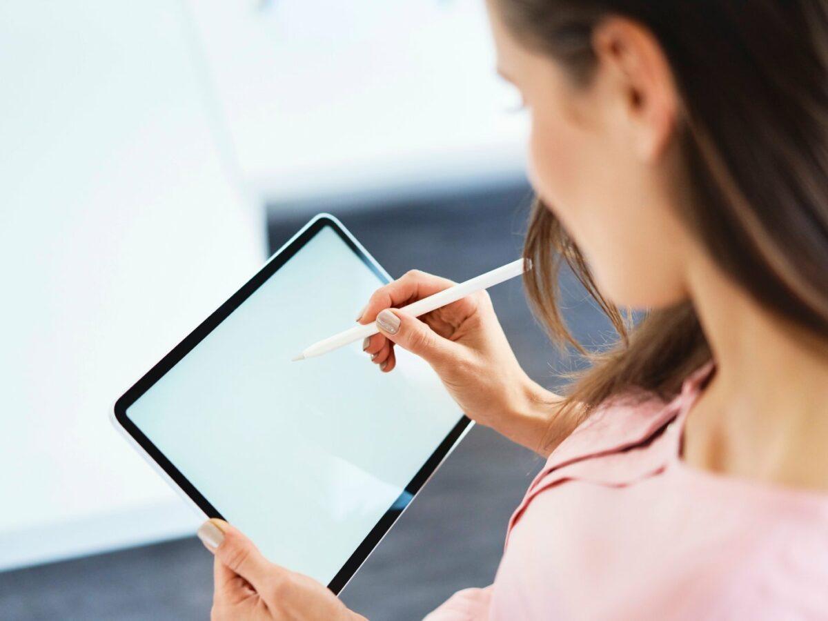 Frau schreibt auf einem Tablet.