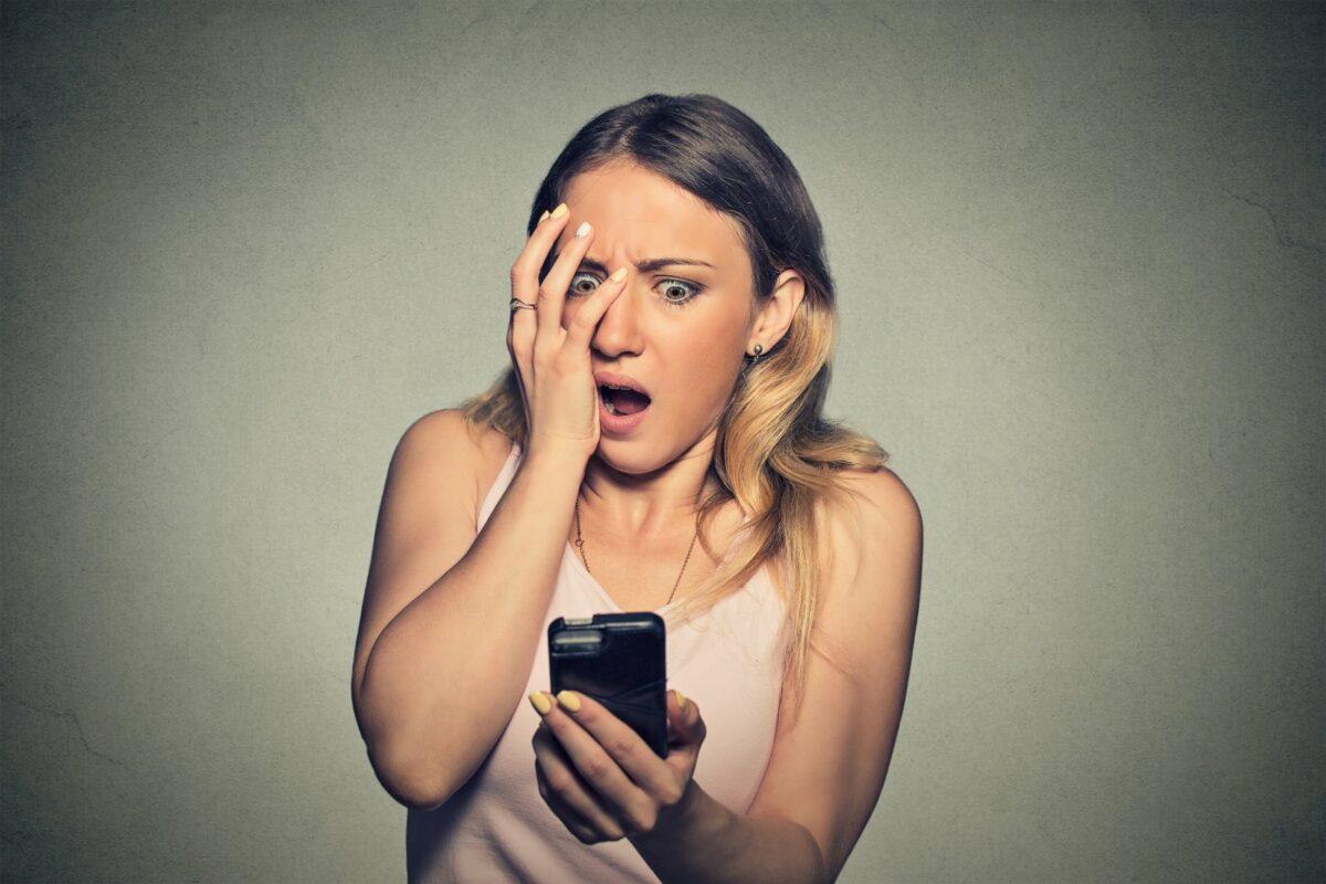 Frau schaut schockiert auf ihr Handy und schlägt sich die Hand ins Gesicht.