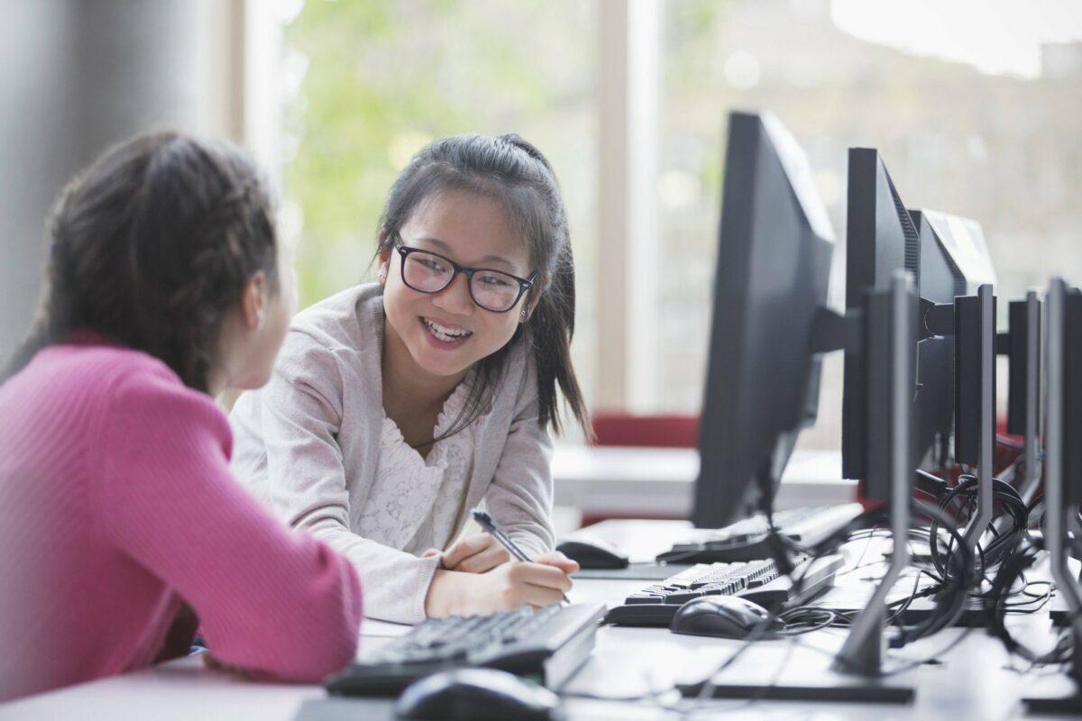 lachende Schülerinnen am Rechner