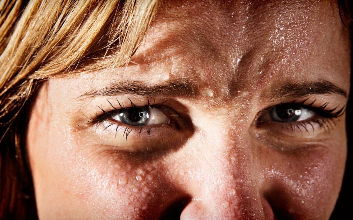 Das Gesicht einer Frau mit Schweißperlen überzogen