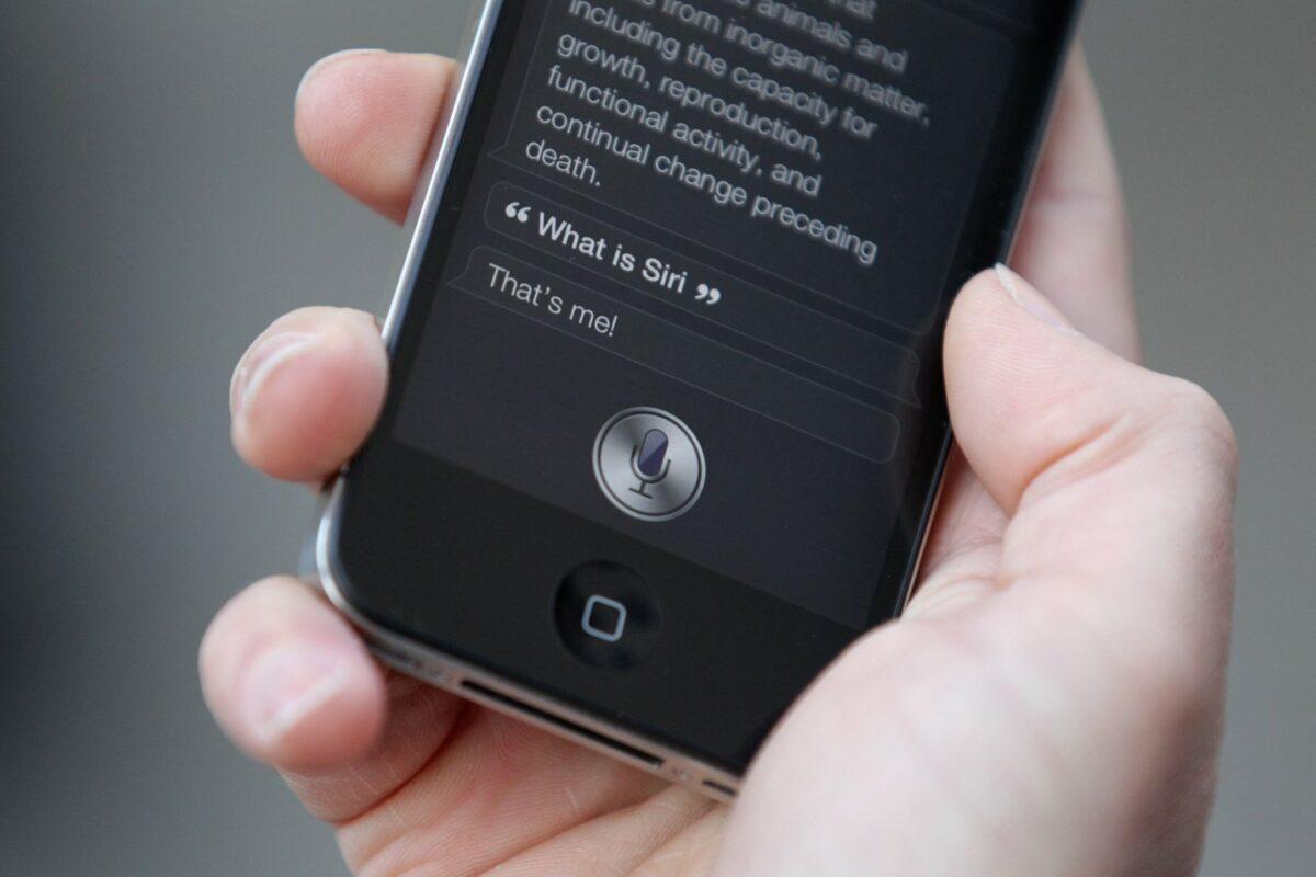 Hand hält iPhone mit Siri in der Hand