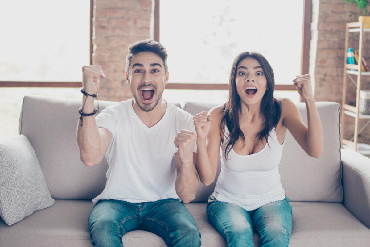Mann und Frau vor TV freuen sich.