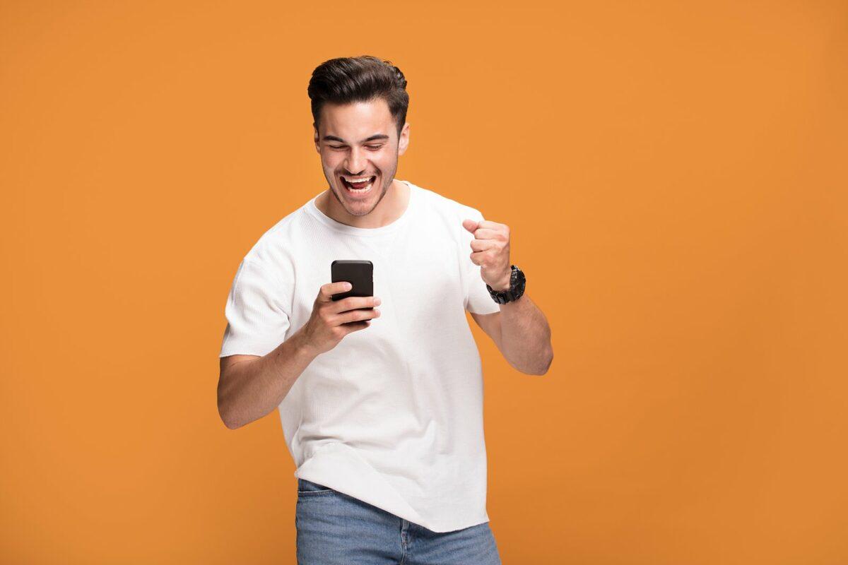 Mann vor orangenem Hintergrund freut sich über seinem Handy.