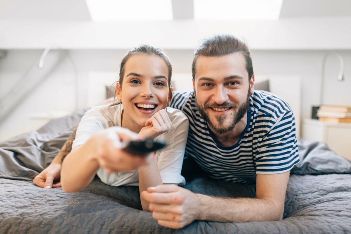 Mann und Frau blicken mit einer Fernbedienung frontal in die Kamera.