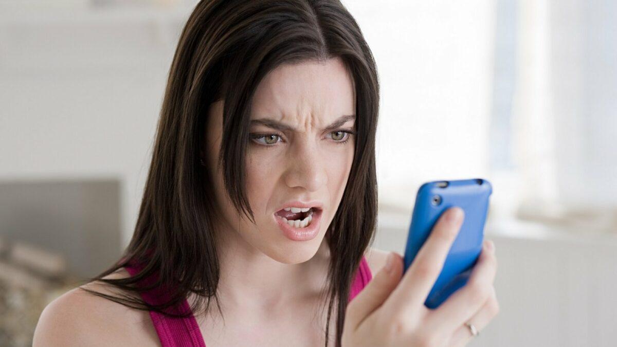 Frau schaut genervt aufs Handy.