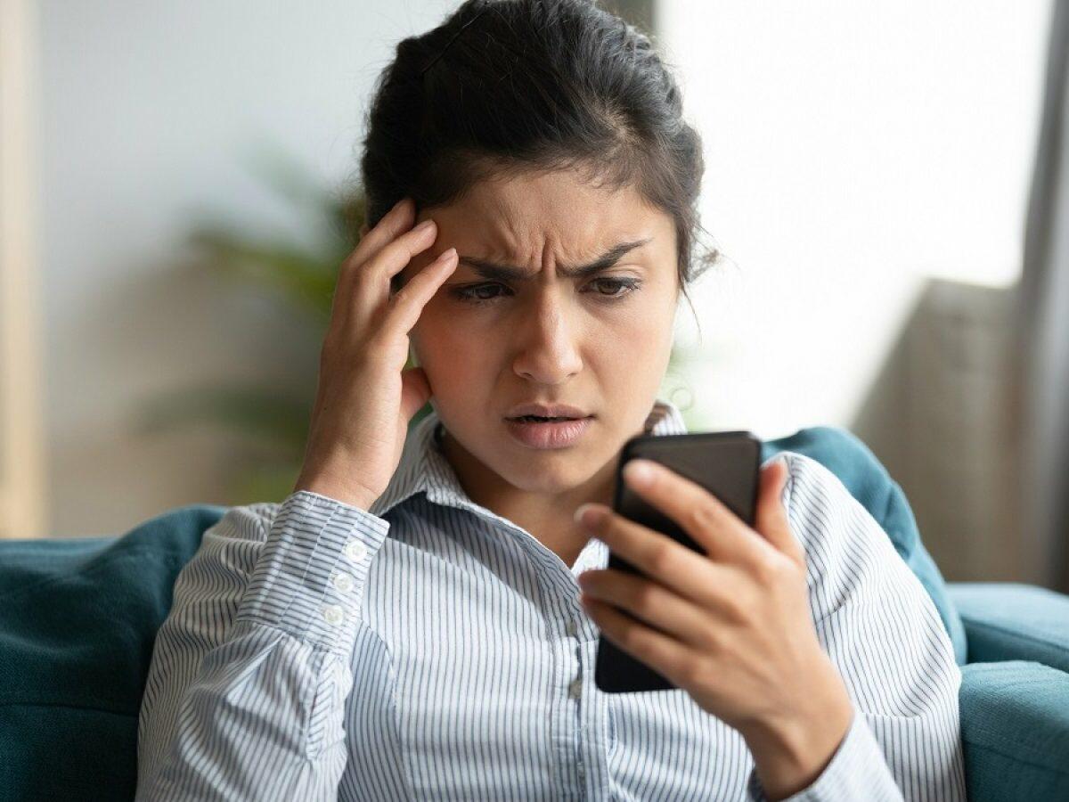 Frau schaut böse auf ihr Handy.