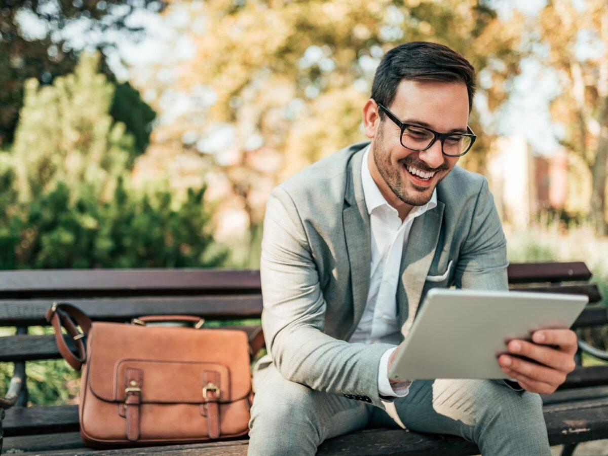 Ein Geschäftsmann sitzt lächelnd auf der Bank und beschäftigt sich mit seinem Tablet.
