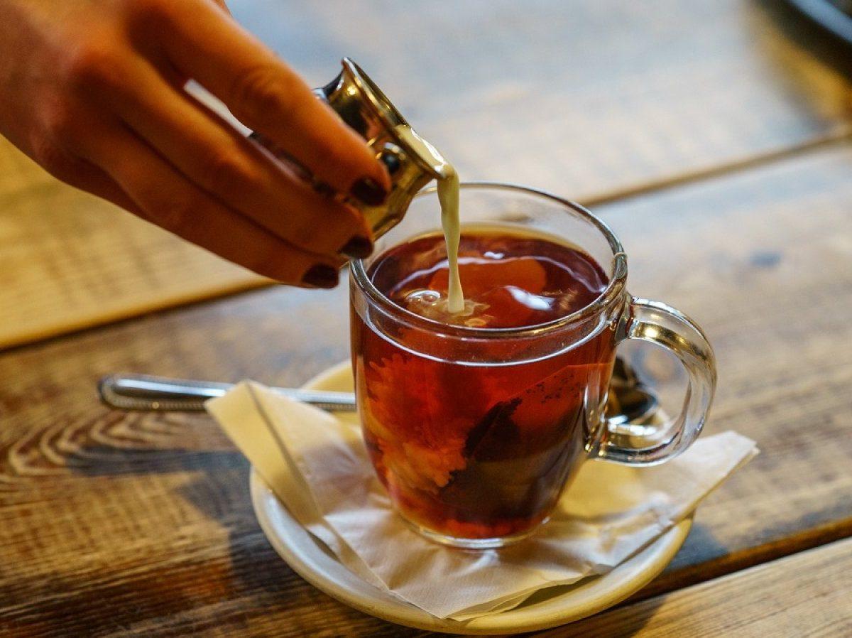 In eine Tasse Tee wird Milch gegossen.