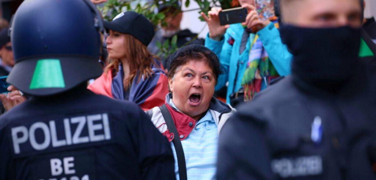 Schreiende Frau zwischen Polizeibeamten