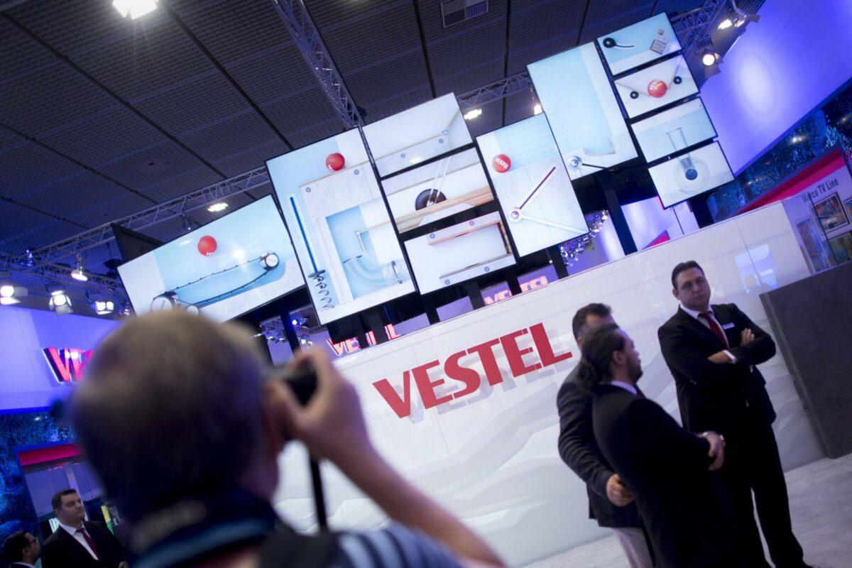 Vetsel Logo mit TVs im Hintergrund auf Messe